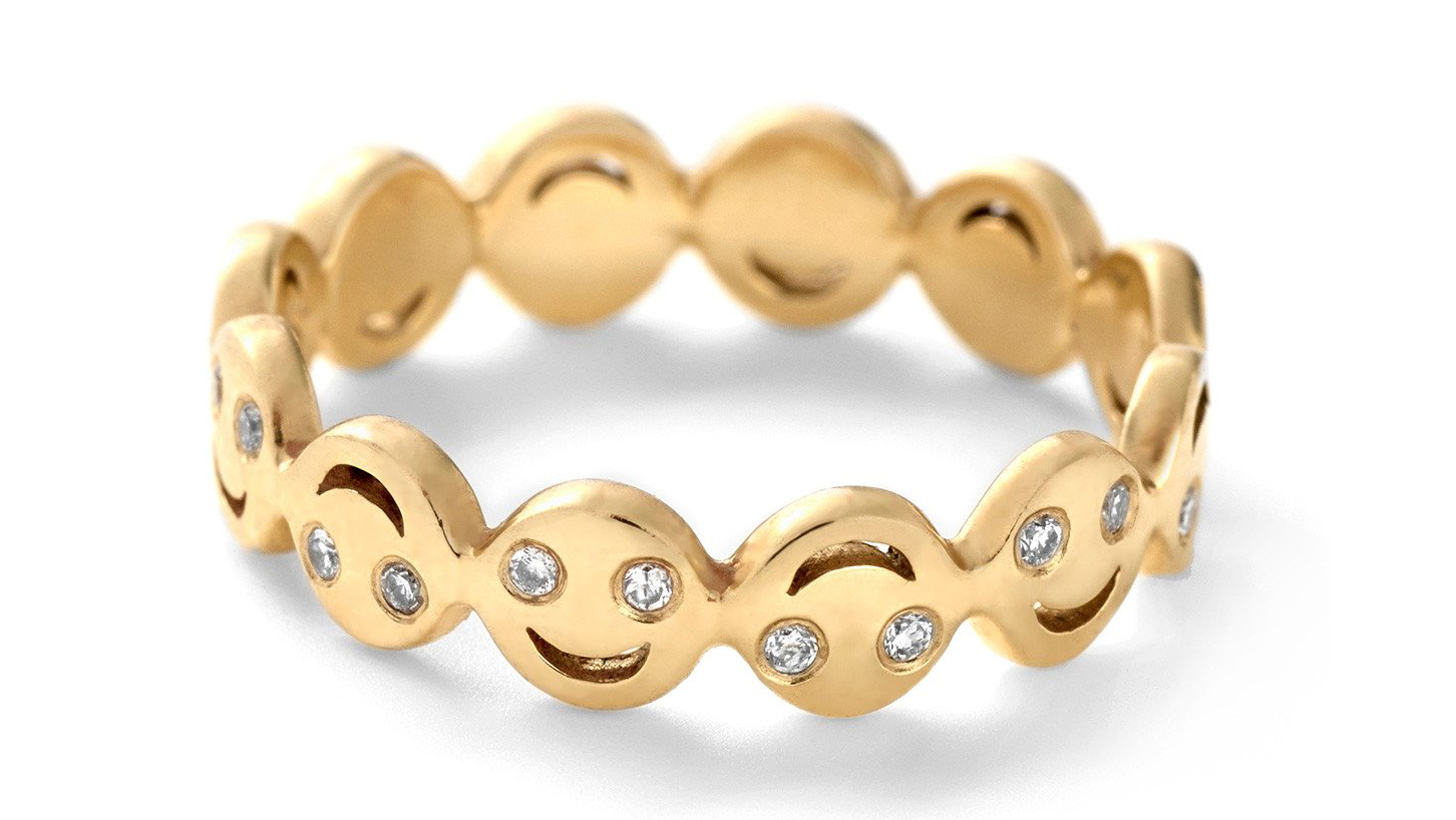 Round cut diamonds set within a gold happy face diamond emoji ring from Alison Lou