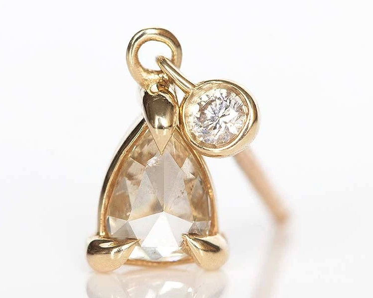 Pear shaped diamond hanging from a single stud earring set in yellow gold