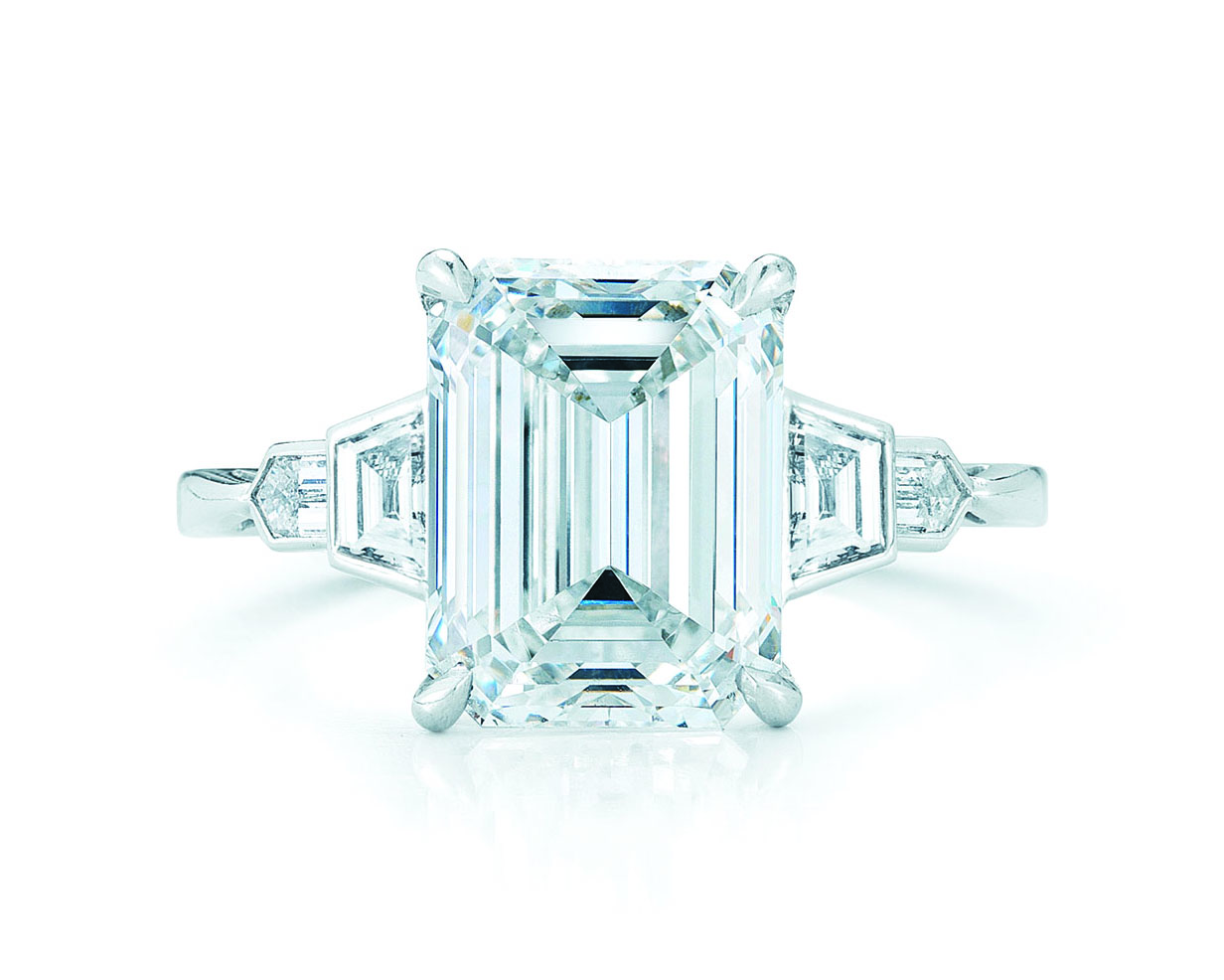 Emerald cut diamond ring with trapezoid side stones in art deco style with a white gold band