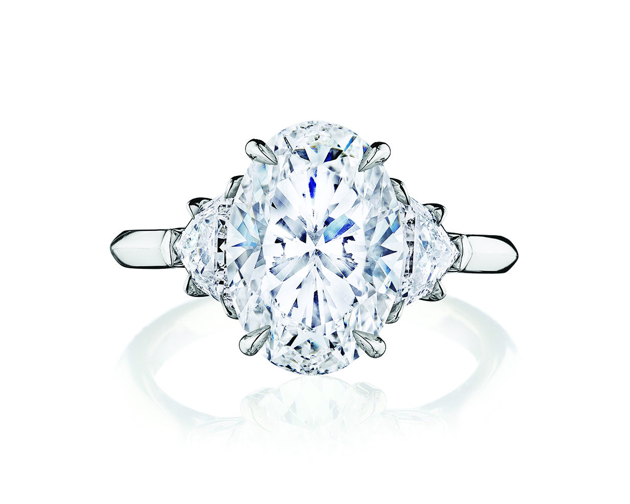 Oval cut diamond center stone engagement ring with two side diamonds on a platinum band