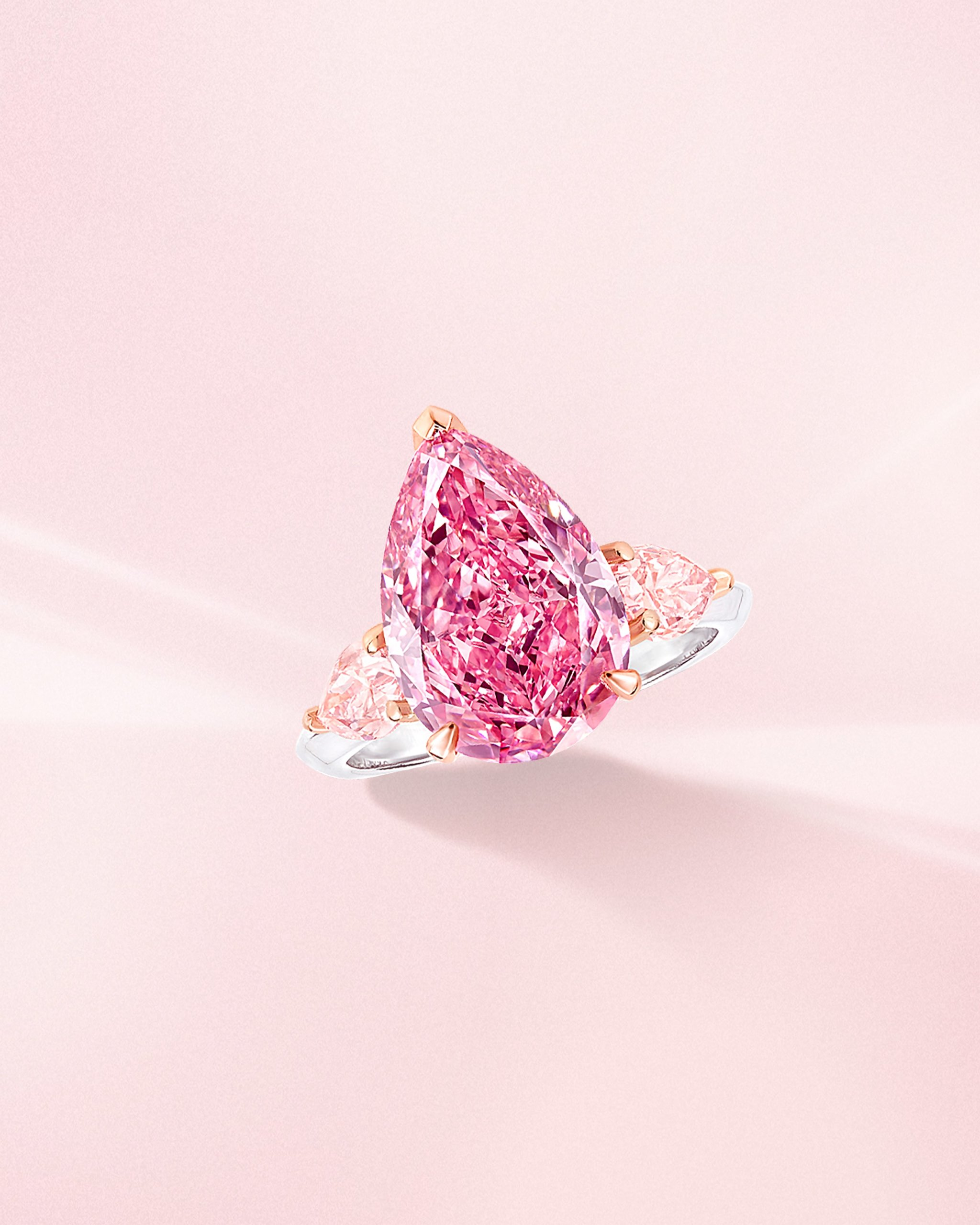 Fancy vivid pink pear shaped diamond ring with side light pink diamonds on a platinum band from Graff