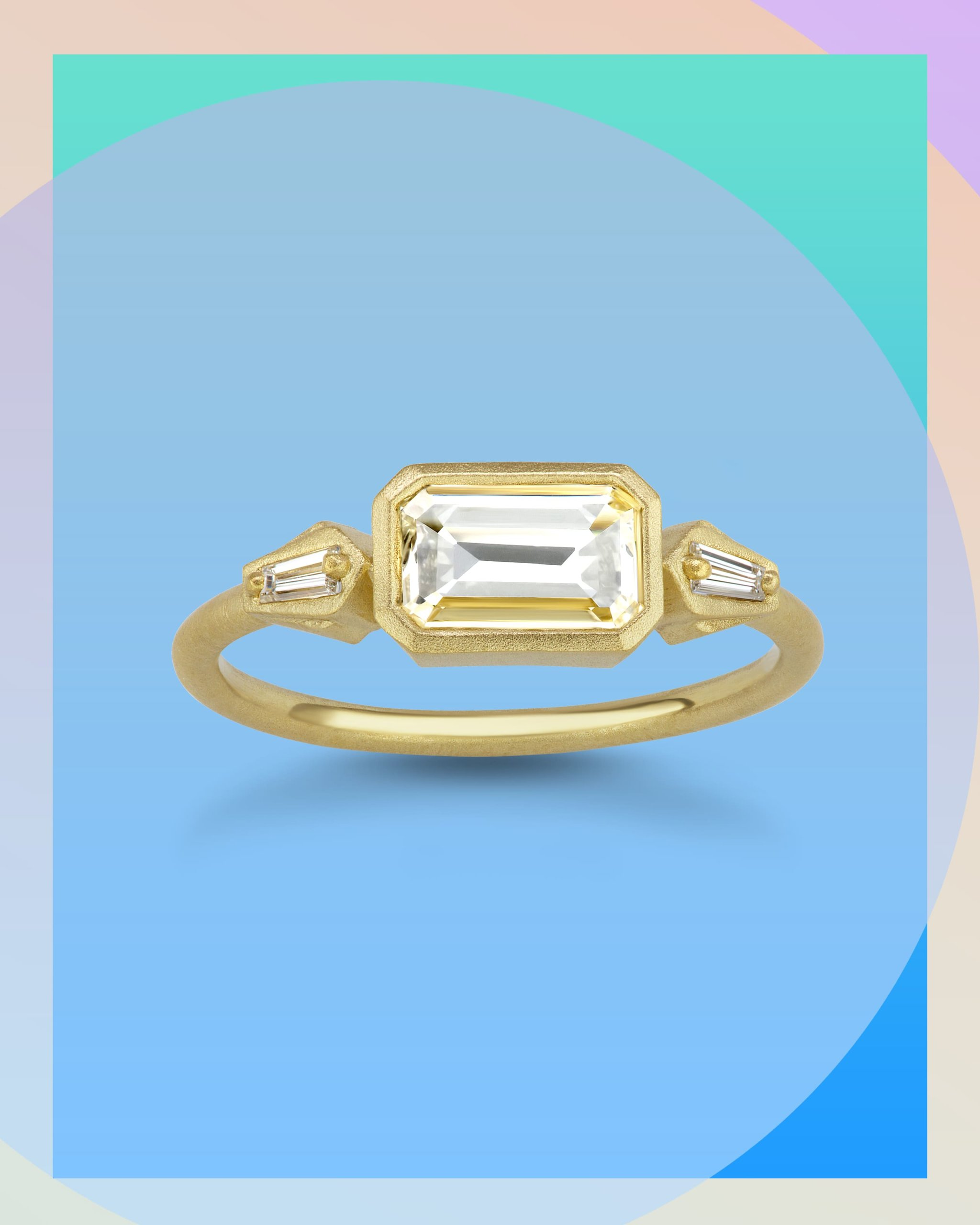 Emerald cut diamond hugged by baguette diamonds on an east west engagement ring with a yellow gold band from Michelle Fantaci