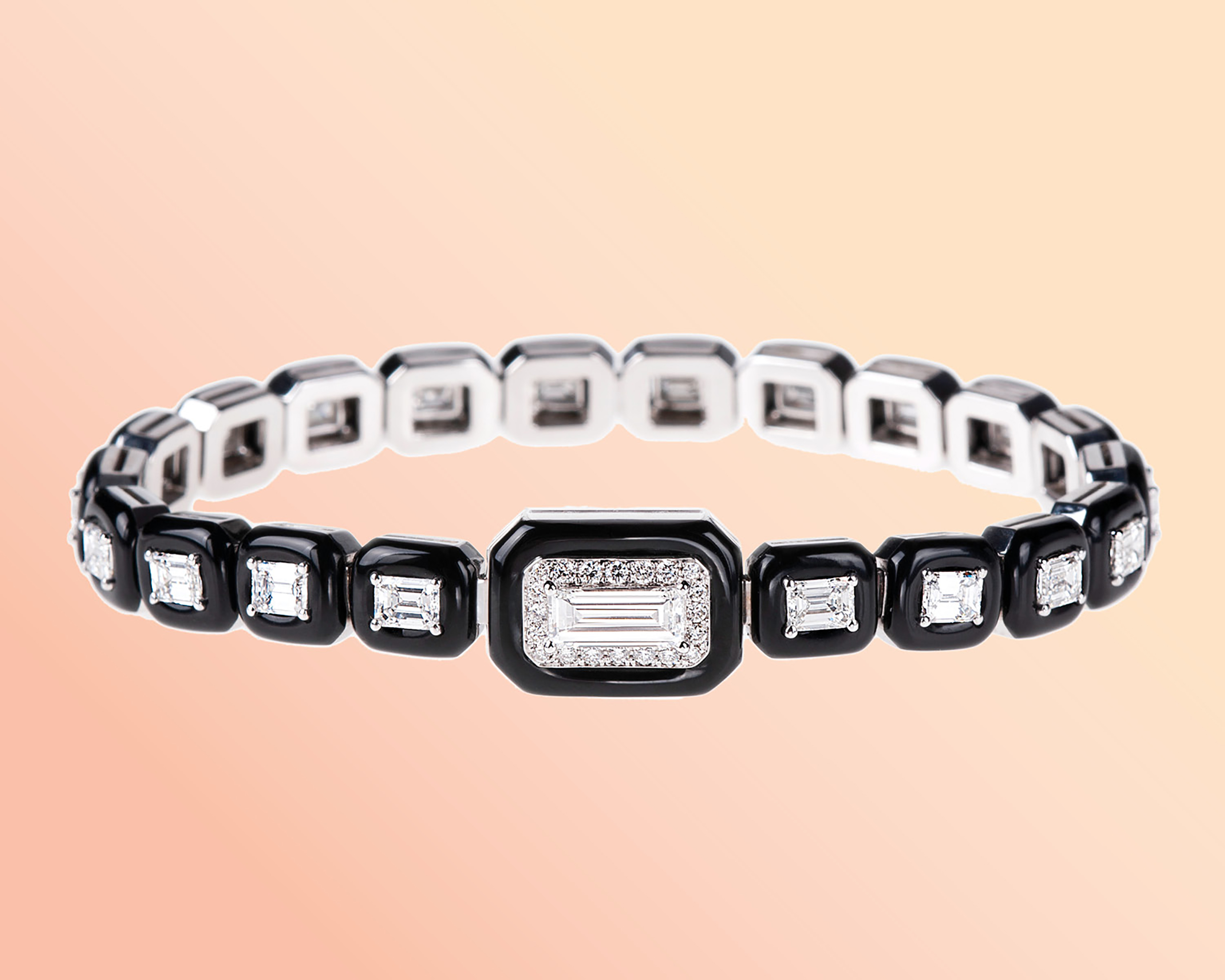 White gold tennis bracelet featuring emerald cut diamonds and black enamel outlines from Nikos Koulis Oui Collection