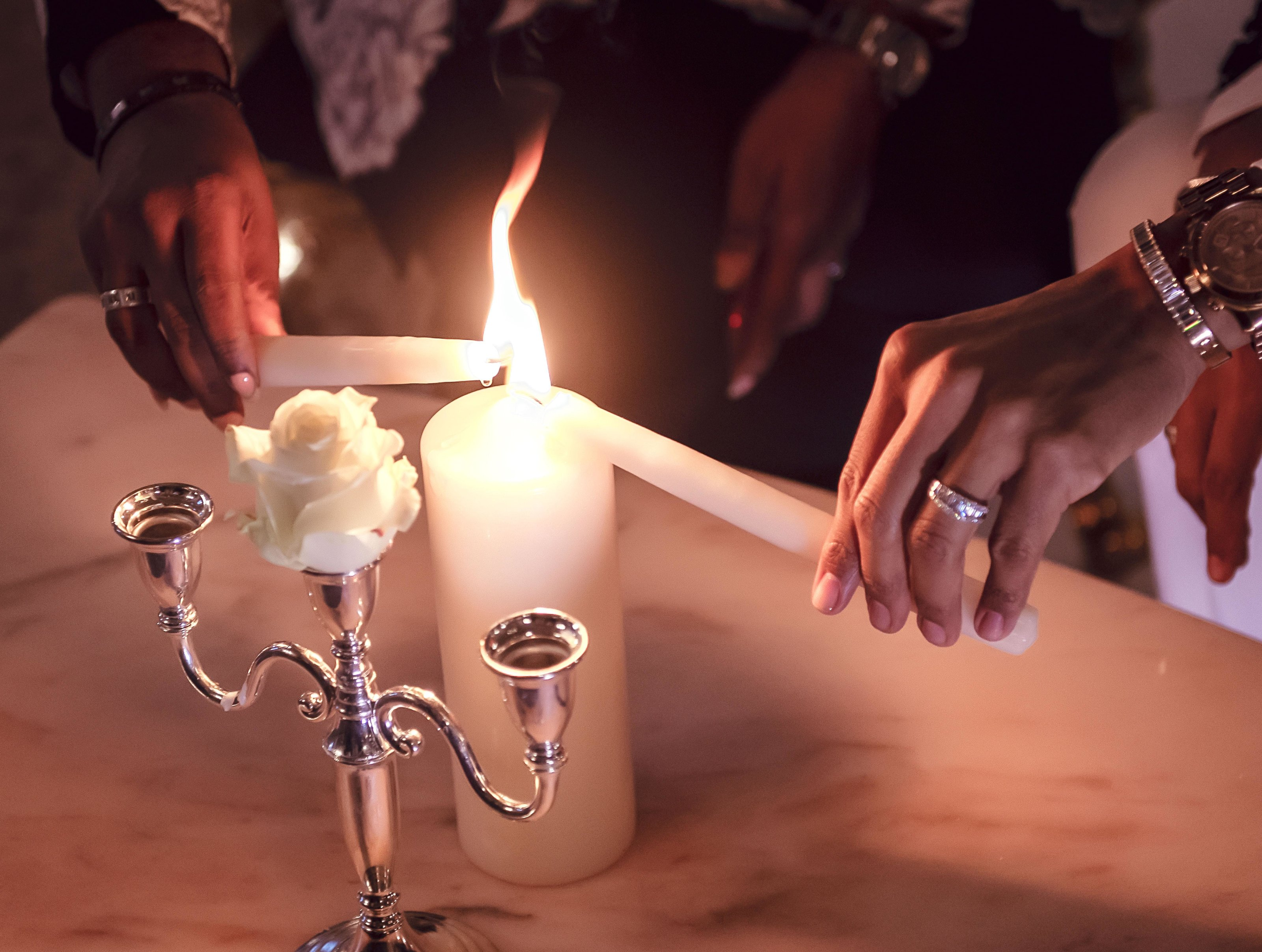 David and Johnny Lester-Massey lighting a ceremony candle wearing white gold baguette diamond ring bands by Atlanta West Jewelry.