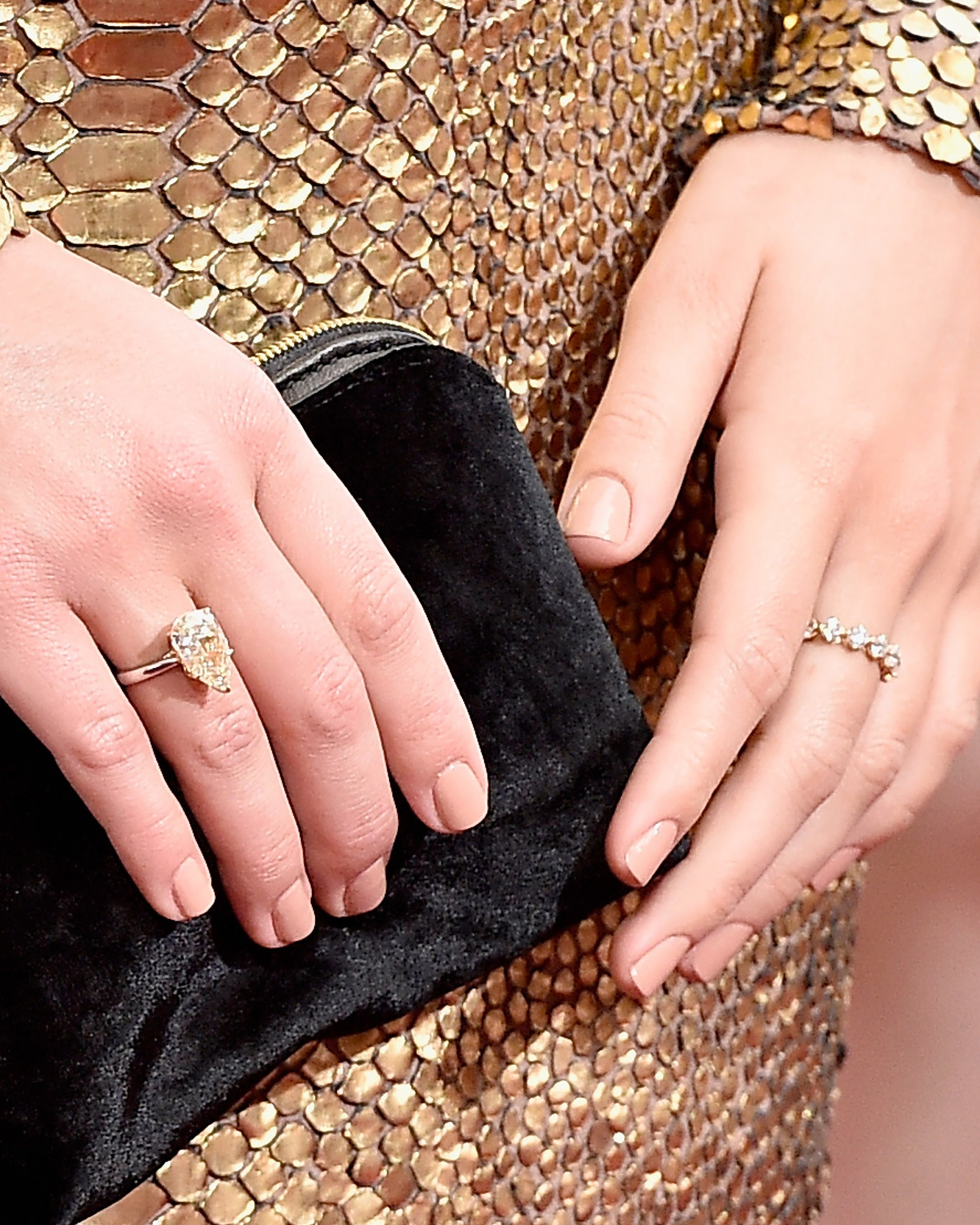 Diamond eternity band in yellow gold and pear shaped yellow diamond ring in white gold worn by Margot Robbie