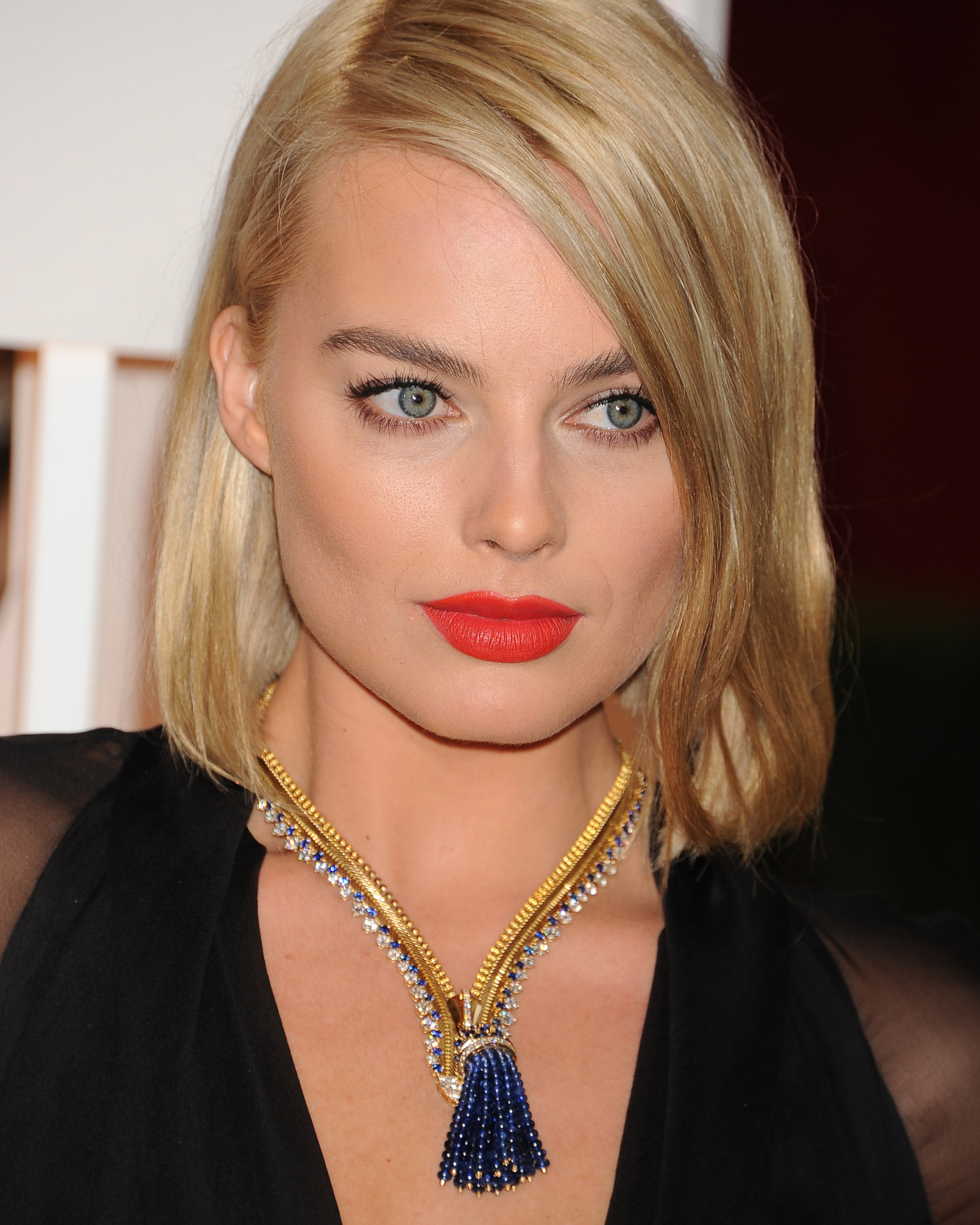 Margot Robbie wearing a zip diamond necklace with round cut diamonds and blue sapphires in gold at the 2015 Academy Awards