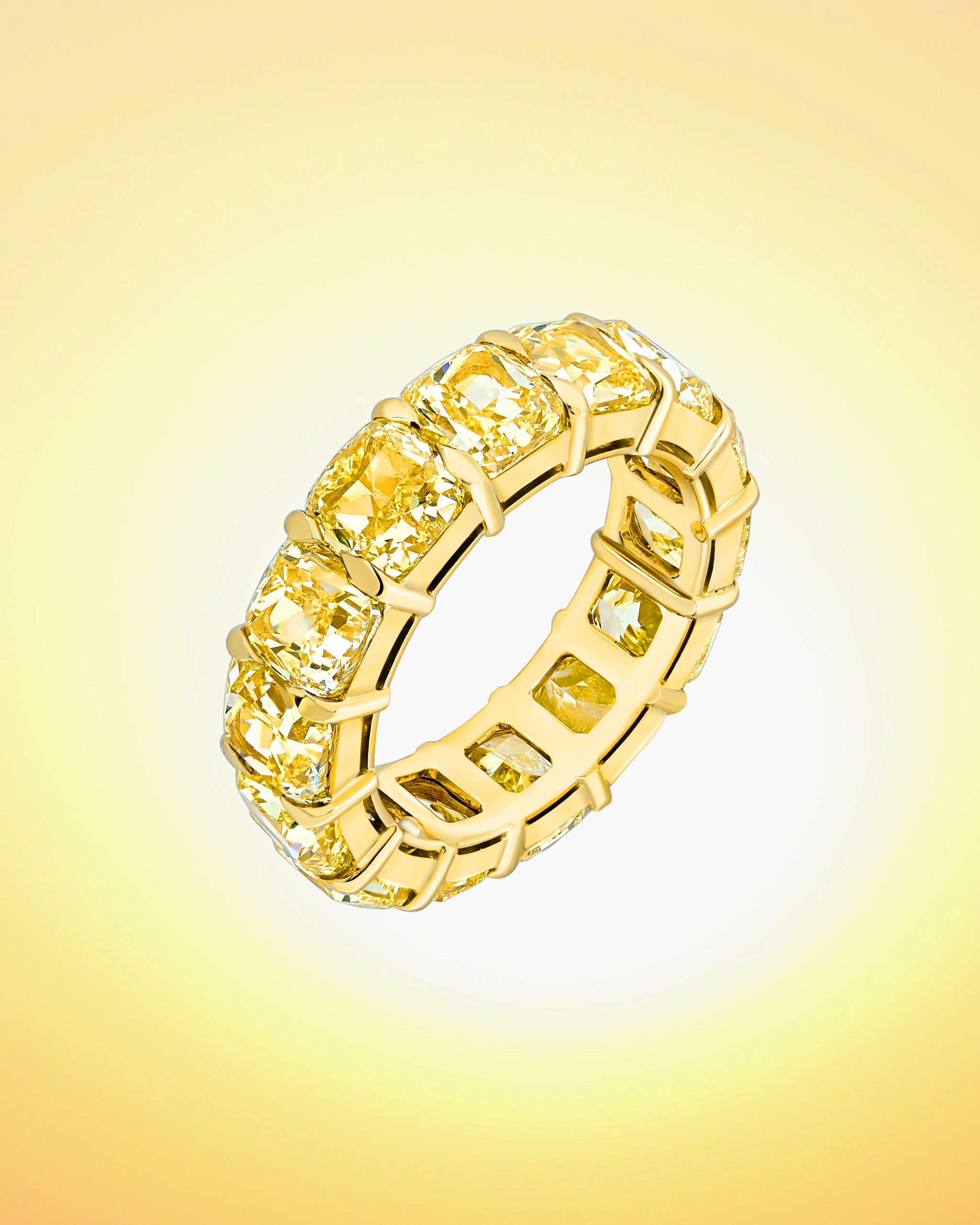 Fancy cut yellow diamond ring in the eternity ring style on a yellow gold band by David Morris
