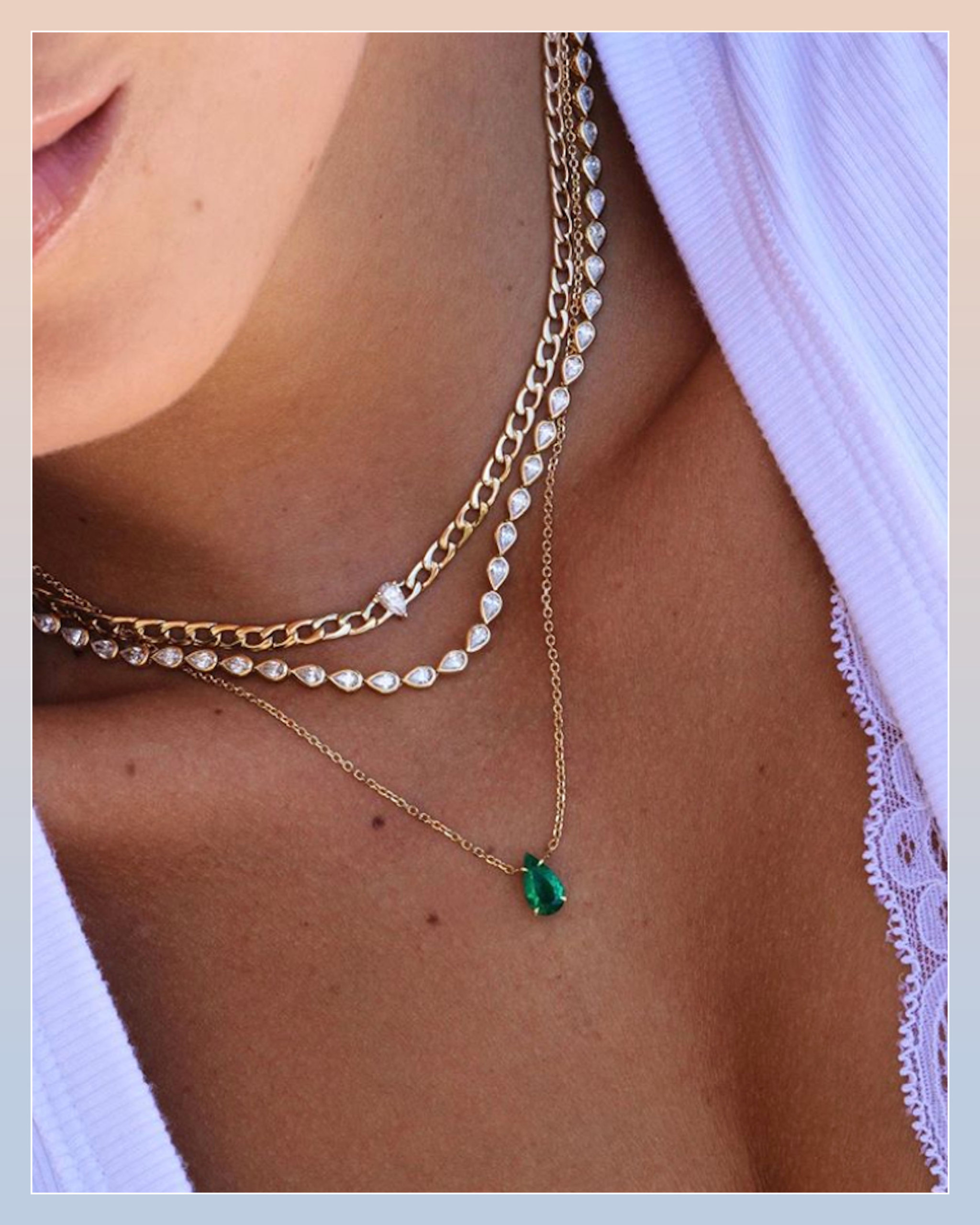 Pear shaped diamond riviere necklace paired with a gold choker necklace and an emerald necklace on a gold chain by Anita Ko