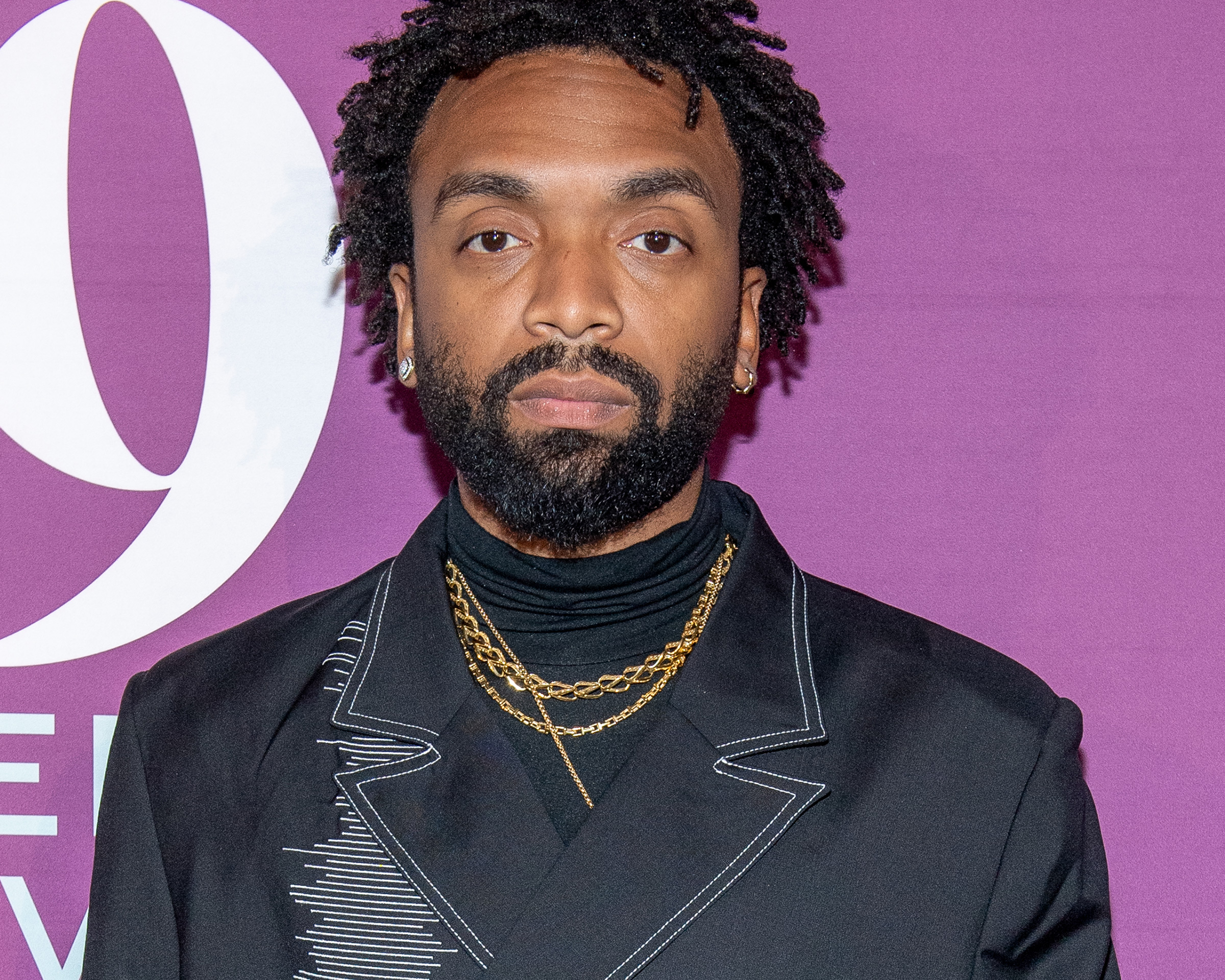 Kerby Jean-Raymond at the 2019 FN Achievement Awards wearing his Pyer Moss suit with John Hardy gold chain necklaces, a diamond Cuban link ring and a white and yellow diamond ring by Shelley & Co