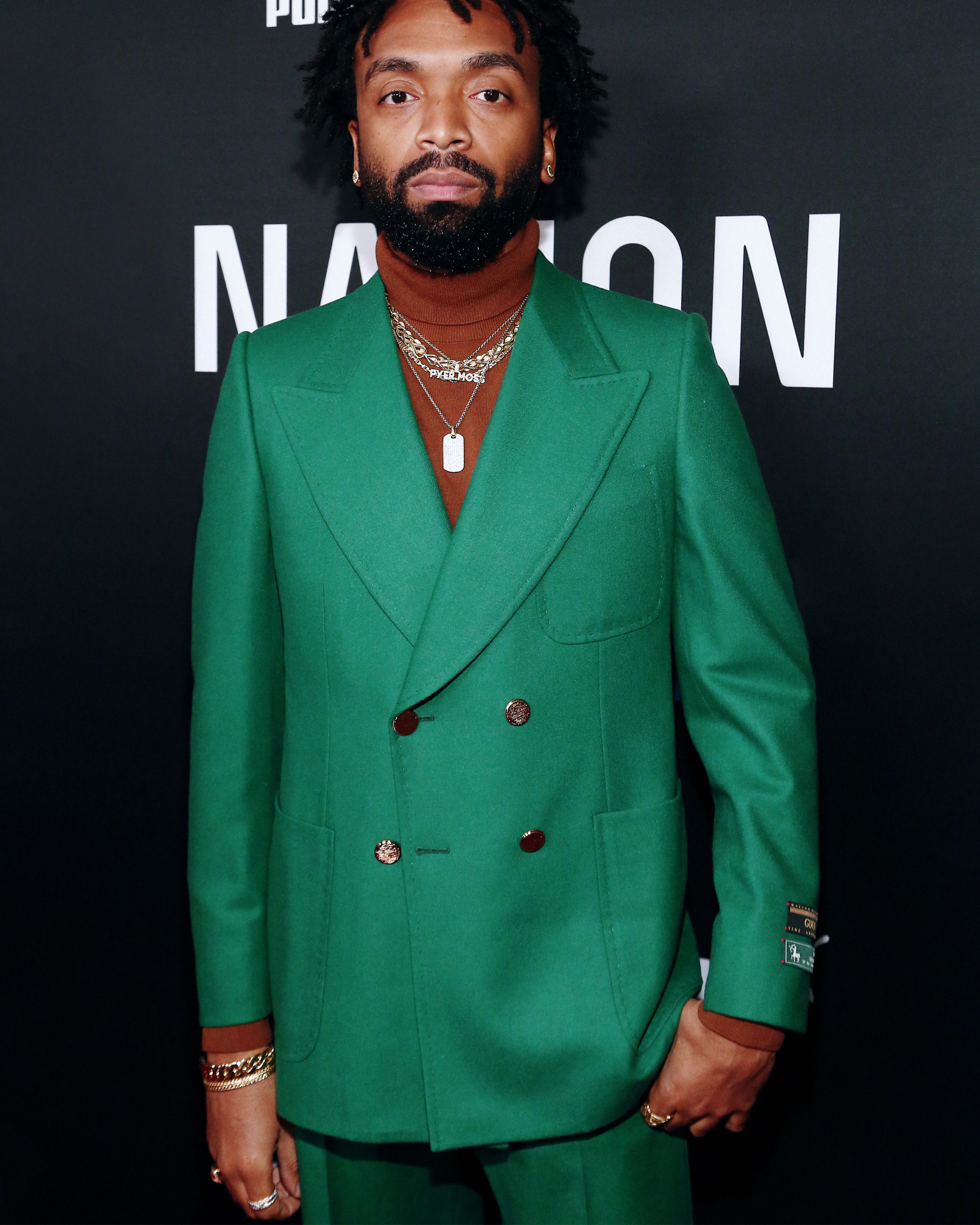 Kerby Jean-Raymond at the 2020 Roc Nation Brunch wearing a kelly green suit and a selection of retro jewelry including a set of gold chain necklaces and custom diamond stud earrings from Shelley & Co