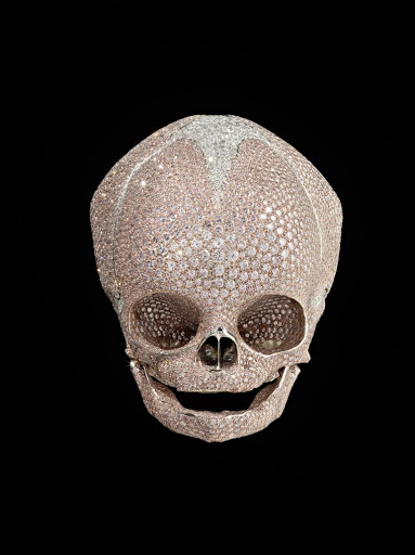Baby platinum diamond skull paved with pink and white diamonds by Damien Hirst